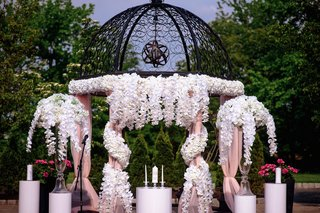 wedding-ceremony-iron-structure-gazebo-with-white-orchid-flowers-and-drapery-outdoor-wedding