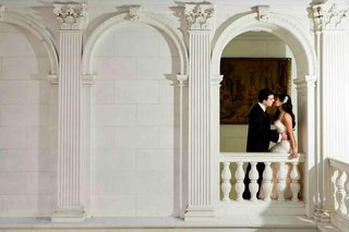 groom-kisses-bride-on-mansion-balcony