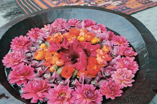 stone-bowl-filled-with-water-and-topped-with-pink-and-purple-flowers