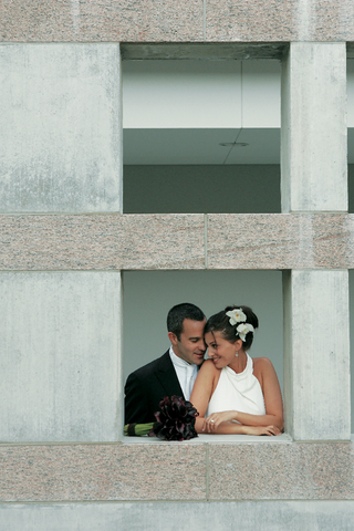 bride-and-groom-looking-at-each-other-in-cement-window