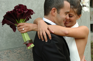 bride-hugs-groom-with-burgundy-calla-lilies