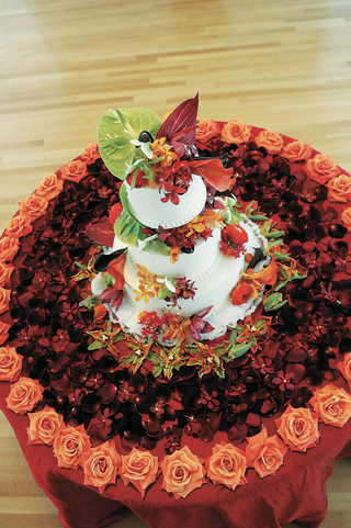 white-cake-with-tropical-flowers-on-flower-covered-cake-table