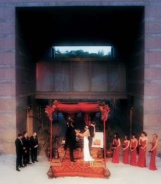 groom-kisses-brides-hand-under-chuppah-at-skirball-cultural-center