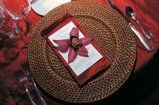 brown-rattan-charger-with-red-napkin-and-orchid