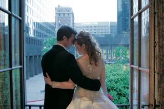 back-of-brides-wedding-dress-in-front-of-city