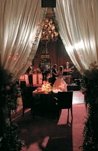 bride-and-groom-dance-under-drapery-and-chandelier