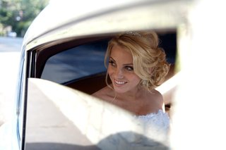 bride-with-updo-in-classic-white-wedding-car