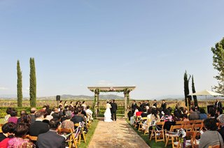bride-and-groom-at-altar-in-front-of-vineyard