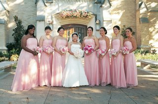 bridesmaids-wearing-strapless-light-pink-gowns-and-carrying-pink-bouquets