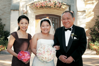 bride-stands-with-father-and-mother-holding-pink-bouquet