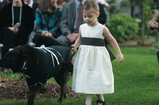 black-dog-walks-with-flower-girl-down-grass-aisle