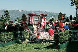 queen-of-hearts-themed-wedding-ceremony-with-red-and-green-topiaries
