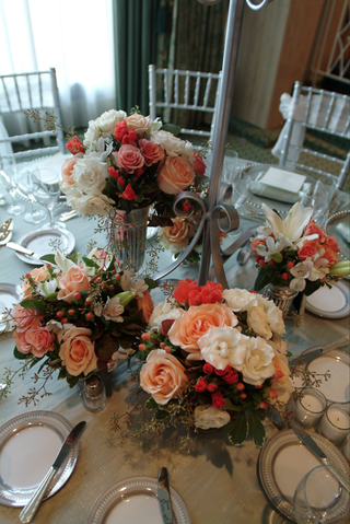 orange-and-pink-flower-arrangements-at-base-of-candelabra
