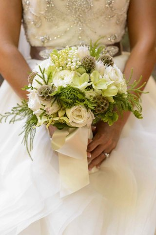 bride-holding-lily-of-the-valley-and-scabiosa-pods