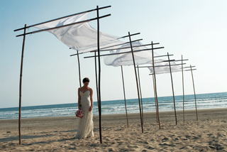 bride-stands-on-beach-under-white-canopy-in-mexico