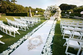 garden-wedding-ceremony-with-white-monogrammed-aisle-runner-and-white-floral-arch