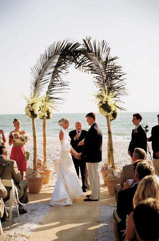 ceremony-arch-made-of-bamboo-flowers-and-palm-fronds