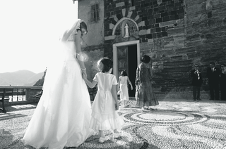 black-and-white-image-of-bride-holding-flower-girls-hand-in-italy