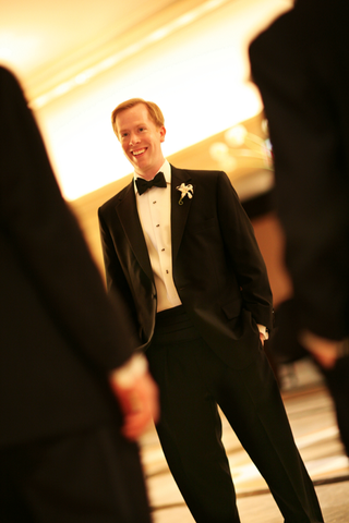 groom-in-a-black-tuxedo-with-a-matching-bow-tie-and-a-white-boutonniere