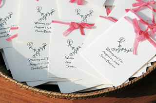 white-wedding-program-with-pink-ribbon-in-wicker-basket
