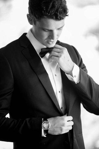 groom-in-black-tuxedo-and-bow-tie-finishes-getting-ready-for-the-wedding