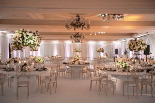 wedding reception carpet ballroom white gold chairs round pedestal tables high low centerpieces classic