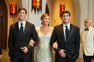 two-groomsmen-escorting-mother-of-bride-down-aisle