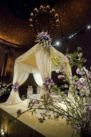 mandap-draped-in-white-fabric-and-decorated-with-purple-flowers-and-greenery