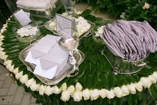 ceremony-presentation-table-covered-by-green-leaves-with-a-rim-or-white-rosebuds