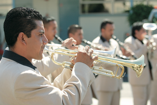 man-playing-trumpet-in-tan-suit-with-black-shirt