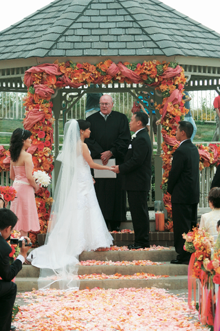 outdoor-wedding-ceremony-in-a-gazebo-decorated-with-orange-and-pink-flowers