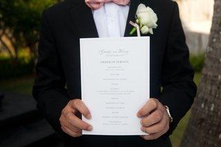 groom-holding-one-sheet-wedding-program