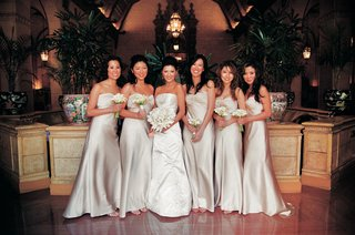 bridesmaids-in-long-off-white-dresses-carrying-bouquets-of-calla-lilies