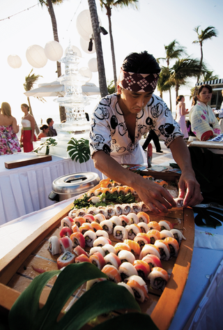 chef-preparing-wooden-boat-filled-with-sushi