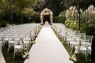 white-aisle-and-chairs-leading-to-floral-chuppah