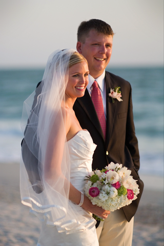 bride-carrying-bouquet-stands-with-groom-on-beach