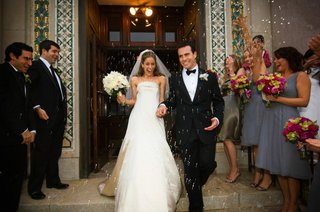 bride-in-a-monique-lhuillier-gown-and-groom-in-a-tuxedo-leaving-ceremony