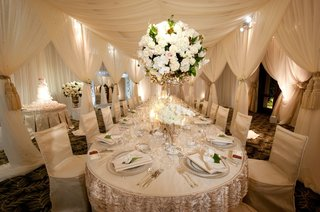 long-reception-table-under-white-canopy-with-large-flower-arrangement