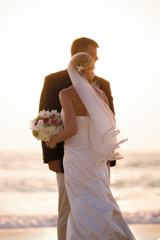 bride-and-groom-stand-on-sand-at-sunset