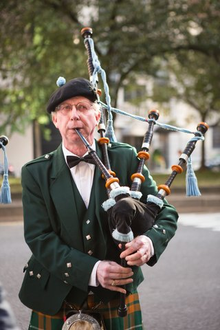 man-in-green-jacket-and-kilt-playing-bagpipes