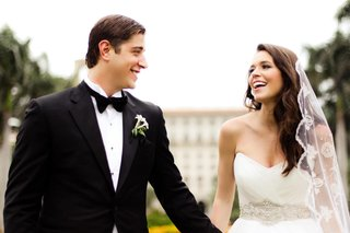 groom-wearing-black-tuxedo-and-bride-wearing-mantilla-veil