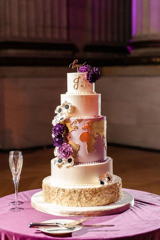 wedding cake with map of world on middle tier sugar flowers anemone rose purple gold white initials love topper
