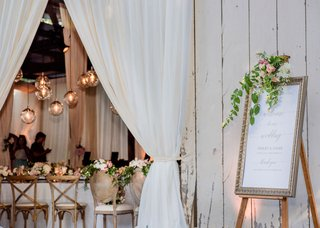 wedding-reception-in-barn-drapery-orb-pendants-framed-welcome-sign-with-greenery-white-pink-flowers