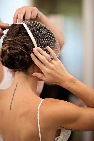 bride-with-updo-and-sapphire-diamond-engagement-ring-puts-on-birdcage-veil