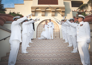 bride-and-groom-in-white-with-navy-uniforms-and-sword-arch