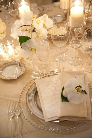 table-setting-with-orchids-and-candlelight-on-neutral-tablecloth