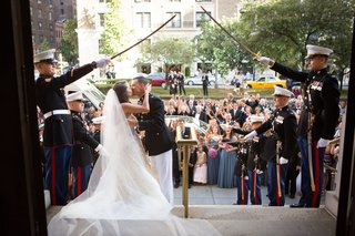 bride-and-groom-kiss-outside-church-with-marines