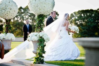 bride-in-a-strapless-pnina-tornai-ball-gown-and-veil-with-groom-in-a-black-tuxedo-exit-ceremony