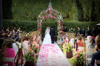 ceremony-in-garden-with-pink-rose-petals-on-aisle-and-pink-and-green-floral-canopy