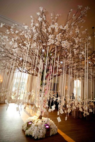 place-cards-were-attached-to-ribbons-suspended-from-tree-branches-decorated-with-white-orchids